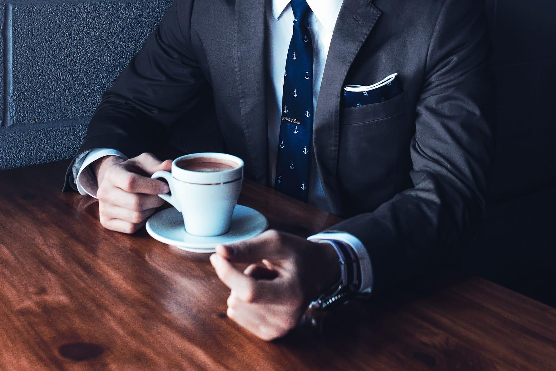 poslovnež pije kavo